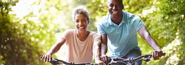 Happy Couple Biking In The Sun